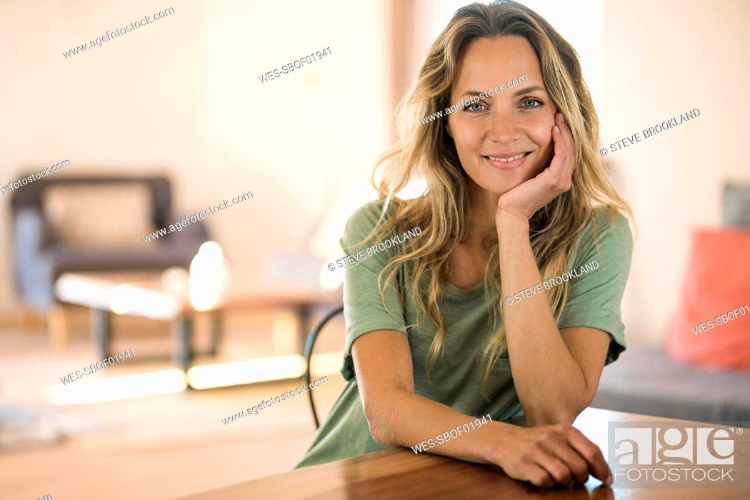 Stock Photo: Portrait of smiling blond woman at home resting her head on the hand.