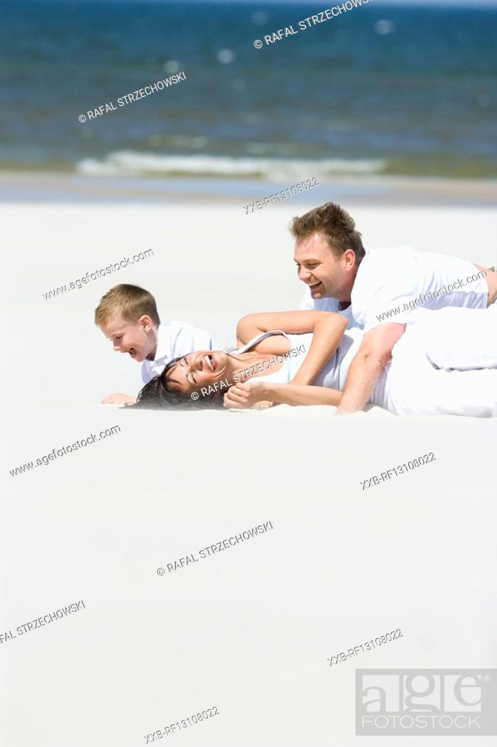 Stock Photo: family playing on beach.