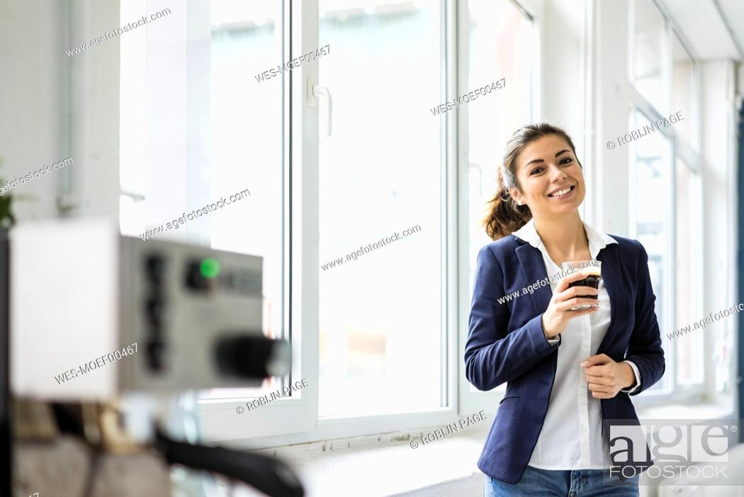 Stock Photo: Portrait of smiling businesswoman having coffee break in a loft.