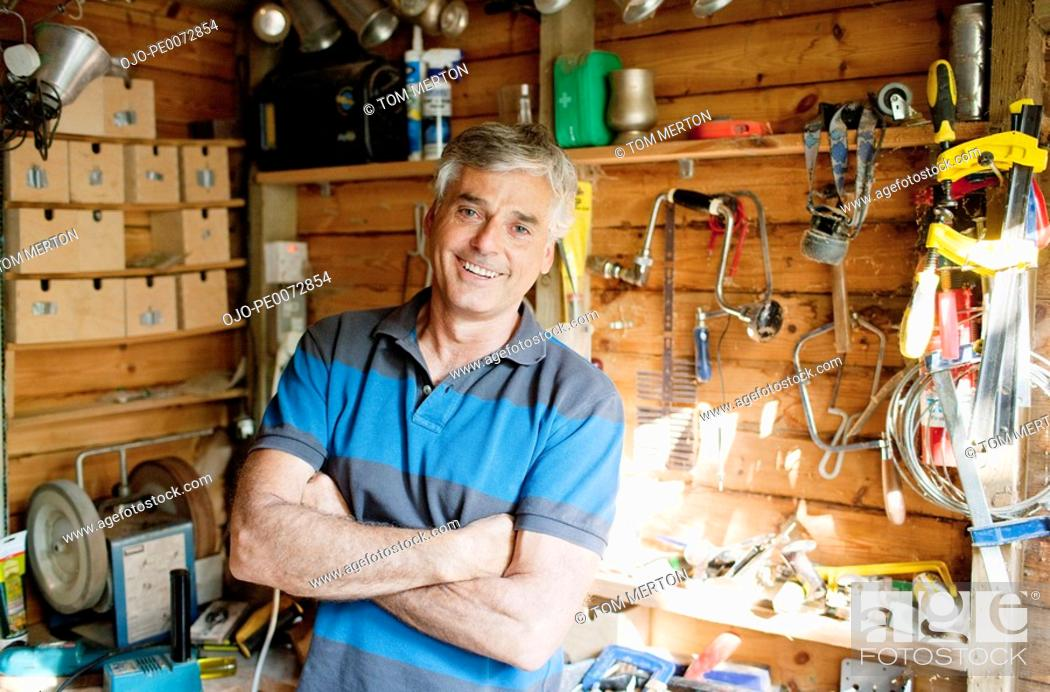 Stock Photo: Smiling man surrounded by tools in workshop.