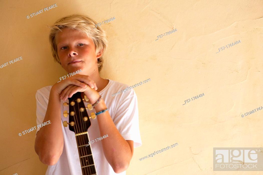 Stock Photo: Teenage boy with his guitar.