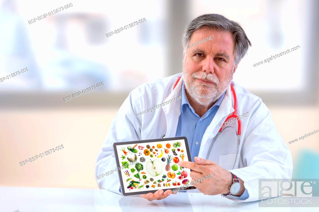 Stock Photo: Doctor nutritionist holdingb digital tablet.with vegetable and fruit on screen.