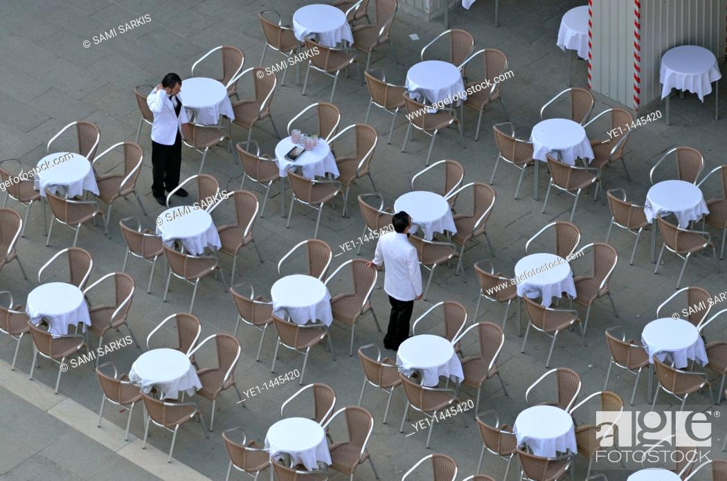 Stock Photo: Waiters at empty cafe terrace on Piazza San Marco, elevated view from the Bell Tower, Venice, Italy.