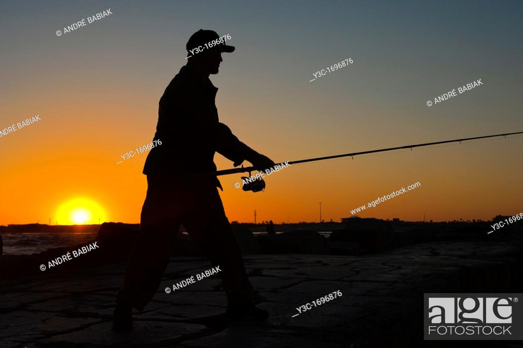 Stock Photo: Sunset silhouette of Fisherman casting the fishing rod.