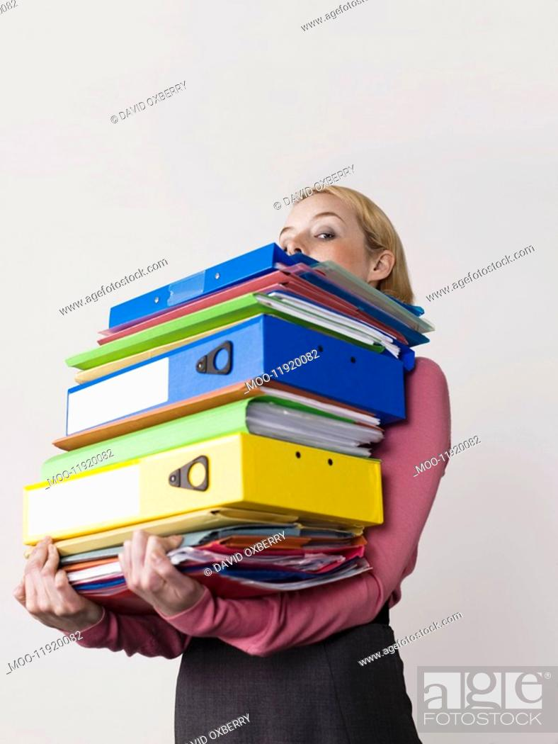 Stock Photo: Female office worker carrying heavy binders on white background.