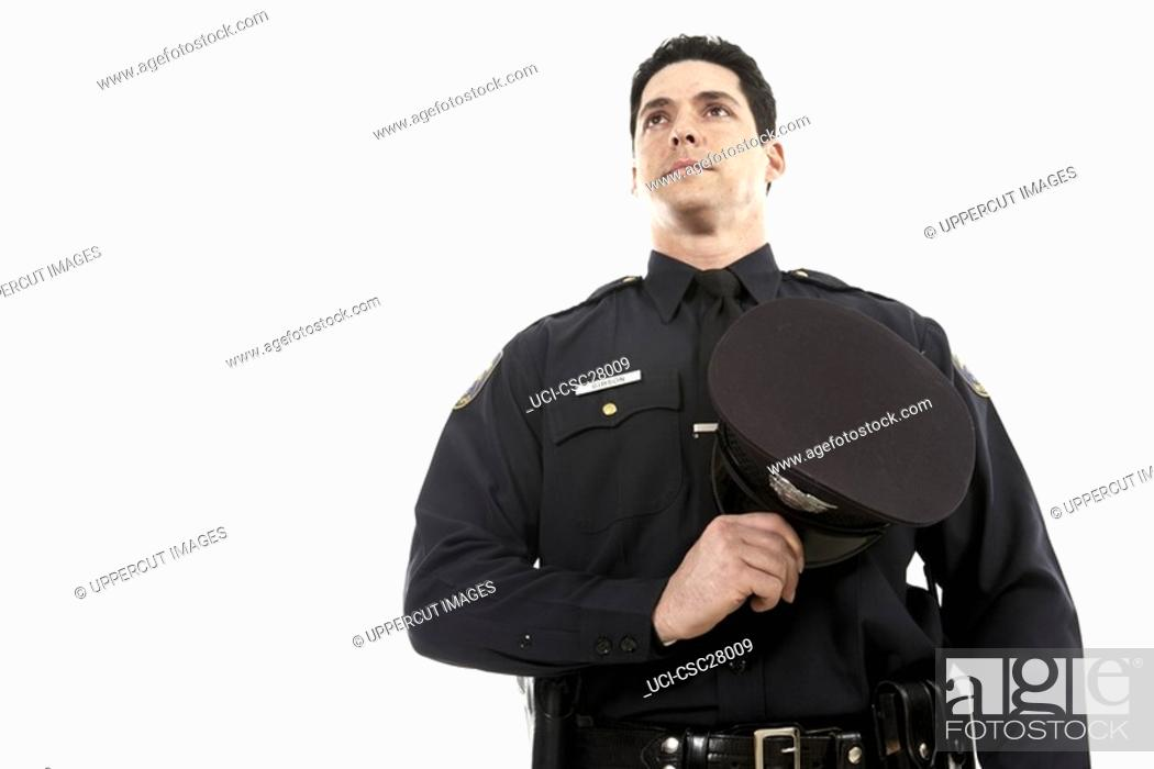 Stock Photo: Male police officer holding his hat over his chest.