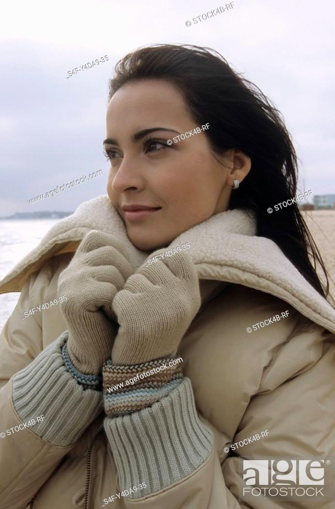 Stock Photo: Young darkhaired Woman cuddling herself into the Collar of her winterly Jacket - Season - Gesture - Beach.