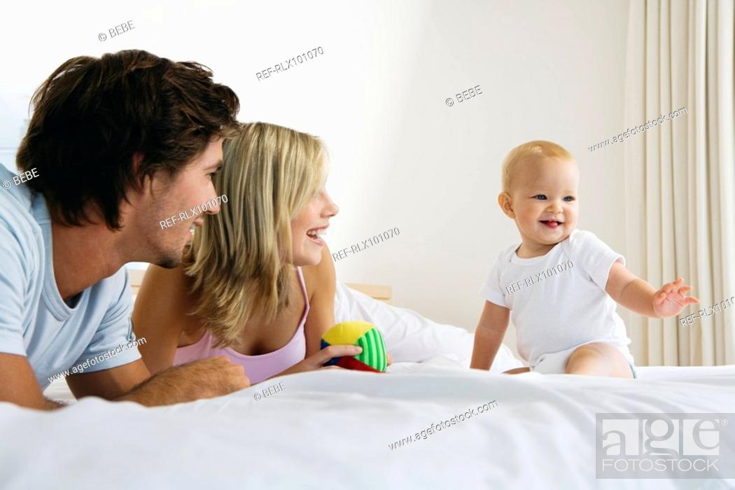 Stock Photo: Young parents on bed with baby 6-12 months and toy, baby sitting up.