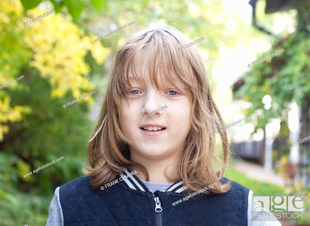 Stock Photo: Portrait of a Boy with Long Blond Hair Outdoors.