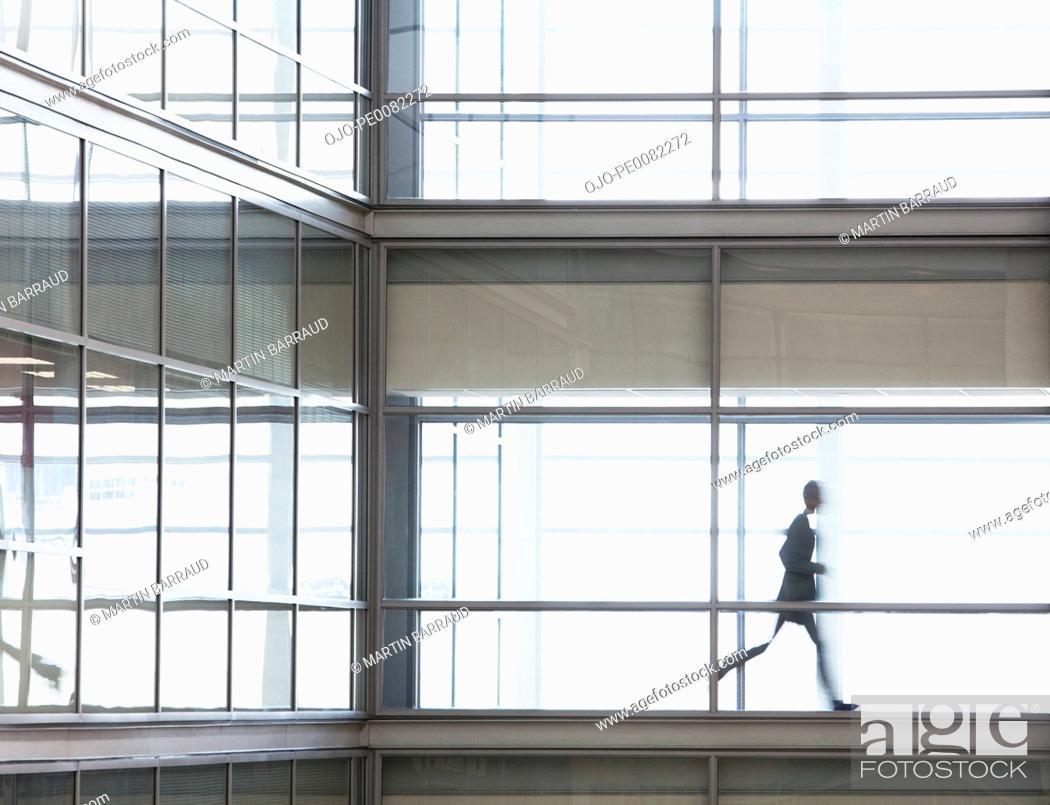 Stock Photo: Businessman running along corridor in office.