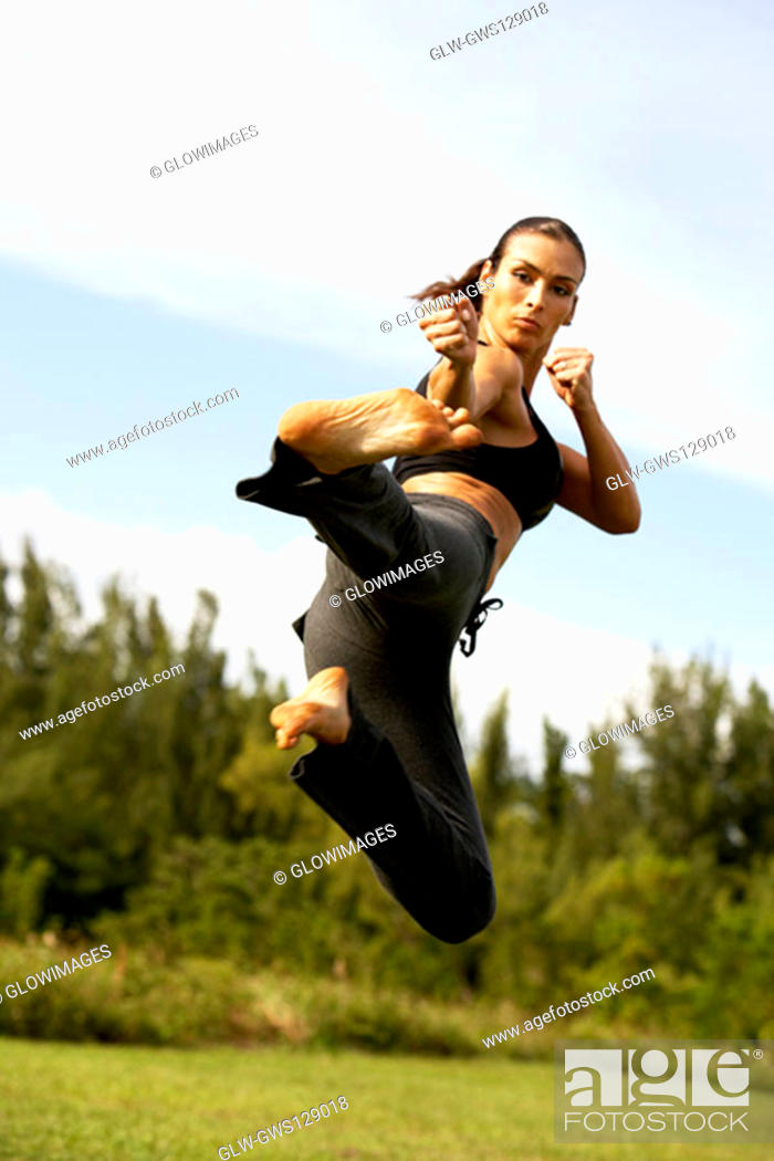 Stock Photo: Low angle view of a mid adult woman practicing martial arts.
