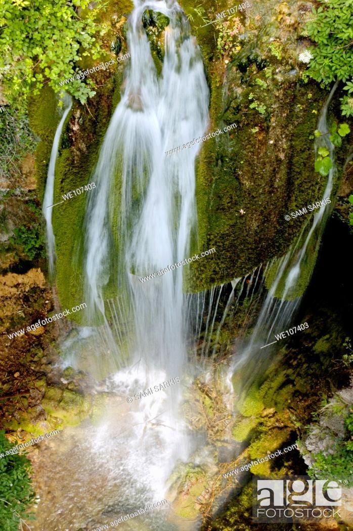 Stock Photo: Little waterfall cascading among mossy rocks.