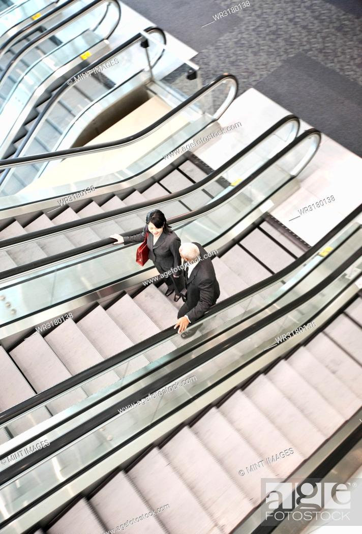 Stock Photo: Mixed race pair of business people on the way to a meeting near a set of escalators.