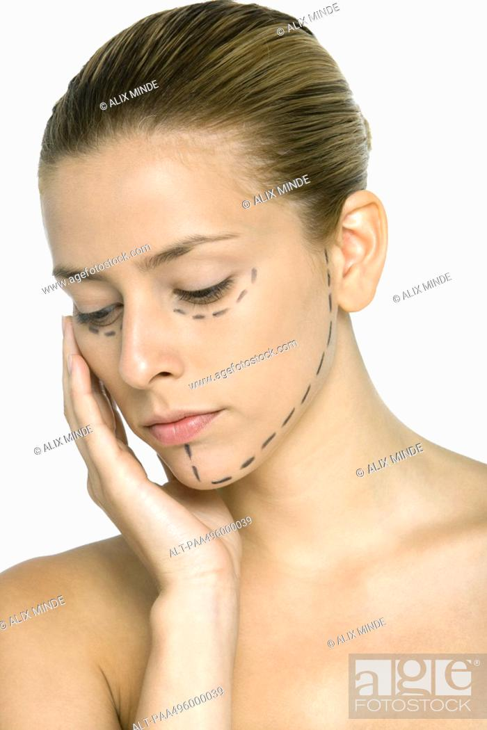 Stock Photo: Woman with plastic surgery markings on face, hand under chin, looking down.