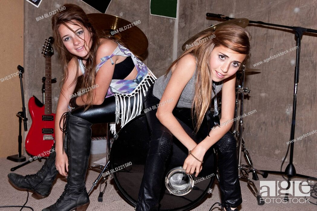 Stock Photo: Girls sitting on drums in rock band.