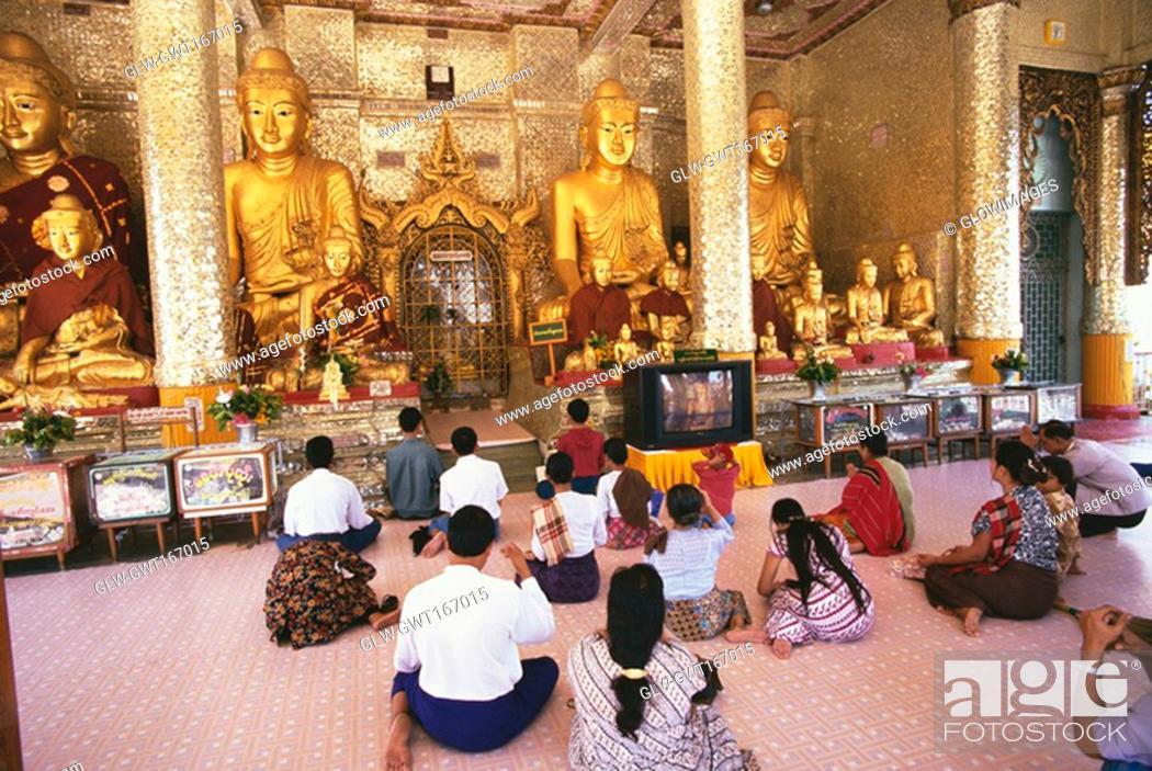 Stock Photo: Rear view of pilgrims praying in a pagoda, Shwedagon Pagoda, Yangon, Myanmar.