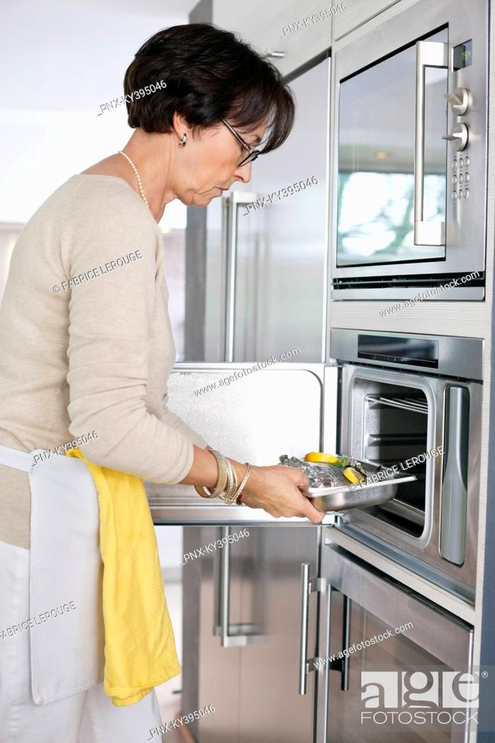 Stock Photo: Elderly woman putting a tray of seafood into an oven.