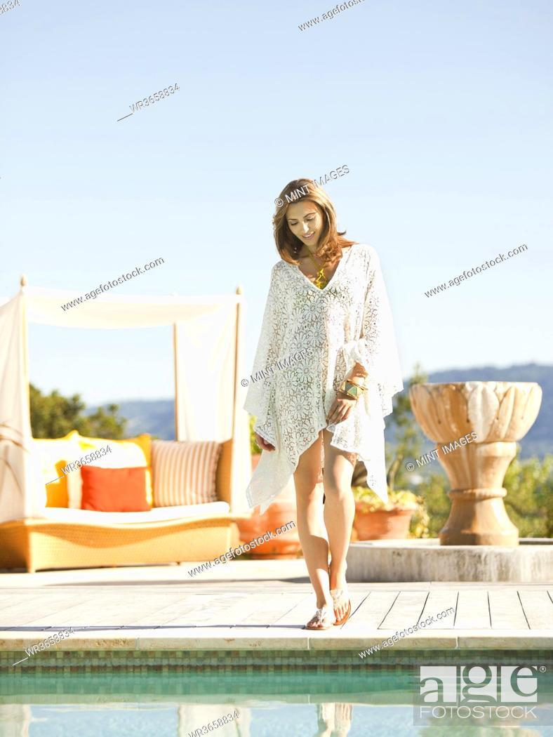 Imagen: Caucasian woman standing near swimming pool.