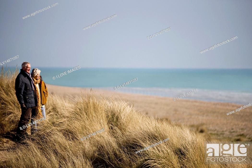 Stock Photo: A senior couple walking amongst sand dunes, looking out to sea.