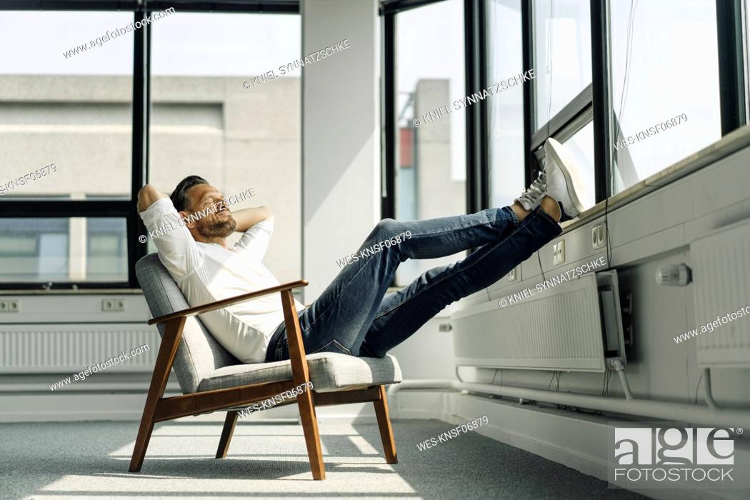 Photo de stock: Mature businessman relaxing at the window in empty office.
