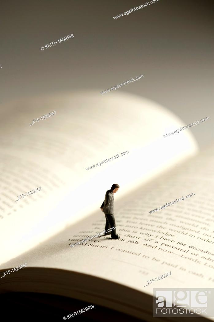 Stock Photo: a small figure of a man walking on an open book - conceptual image for literacy and reading.