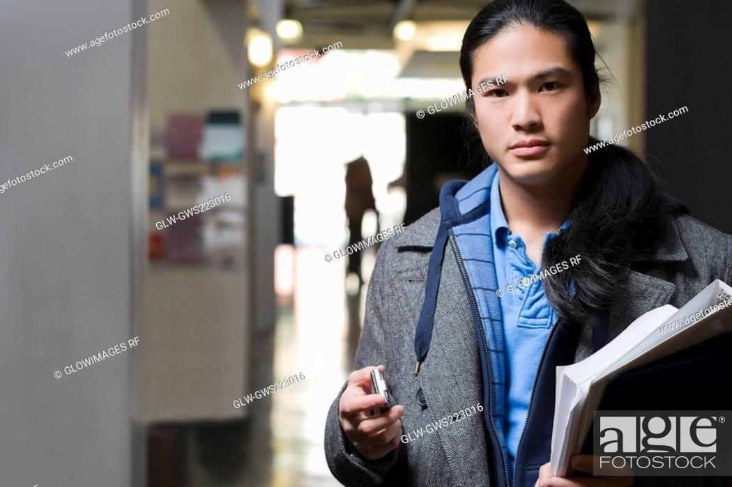 Stock Photo: Portrait of a young man holding textbooks and a mobile phone.