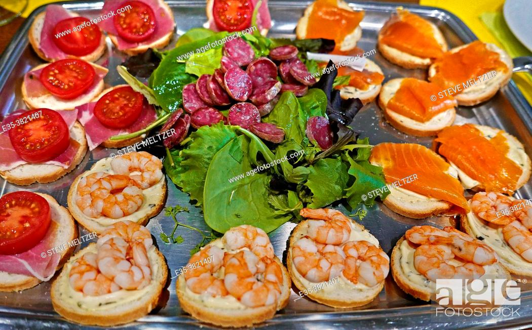 Stock Photo: A plate of mixed cold cuts of salmon, sausage and sausage make up an apero snacks plate to be served before a meal.