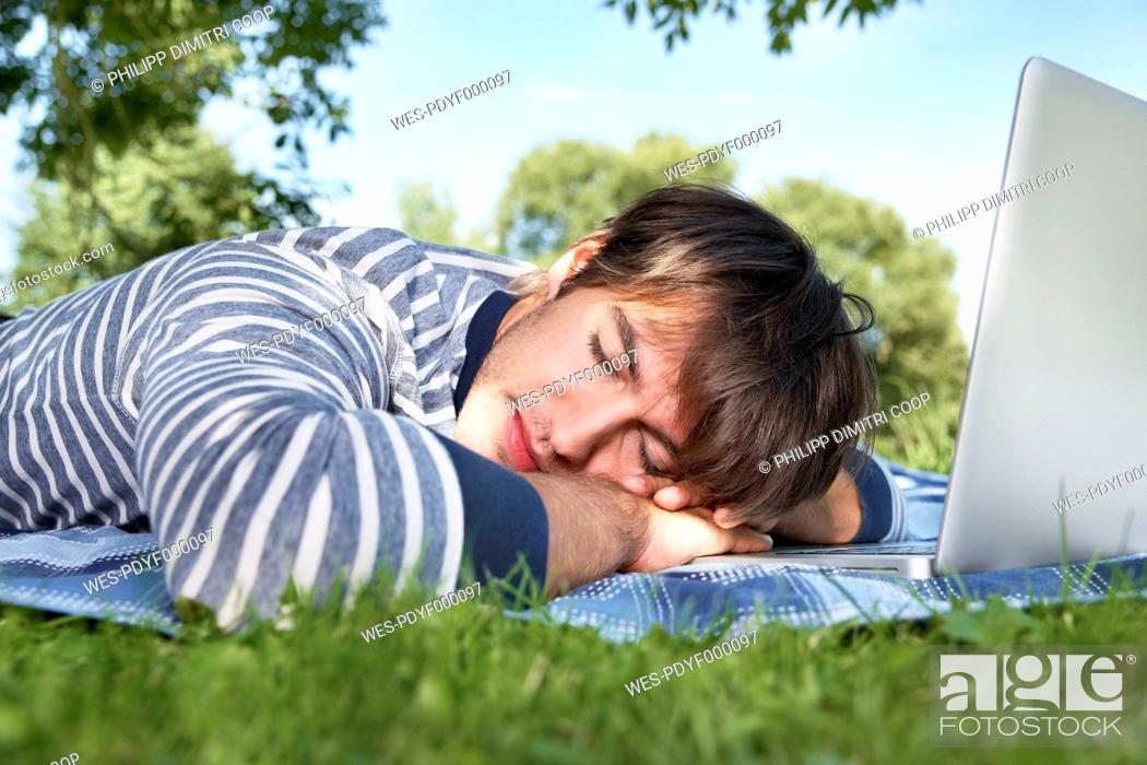 Stock Photo: Germany, Cologne, Young man sleeping in meadow.