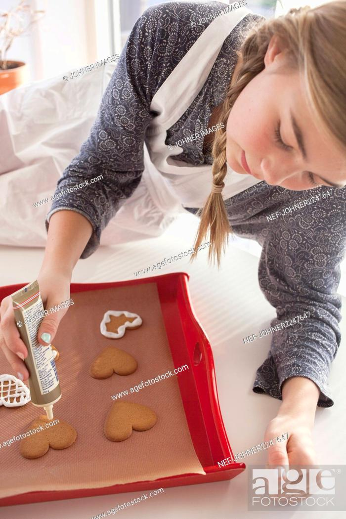 Stock Photo: Girl decorating gingerbread cookies.