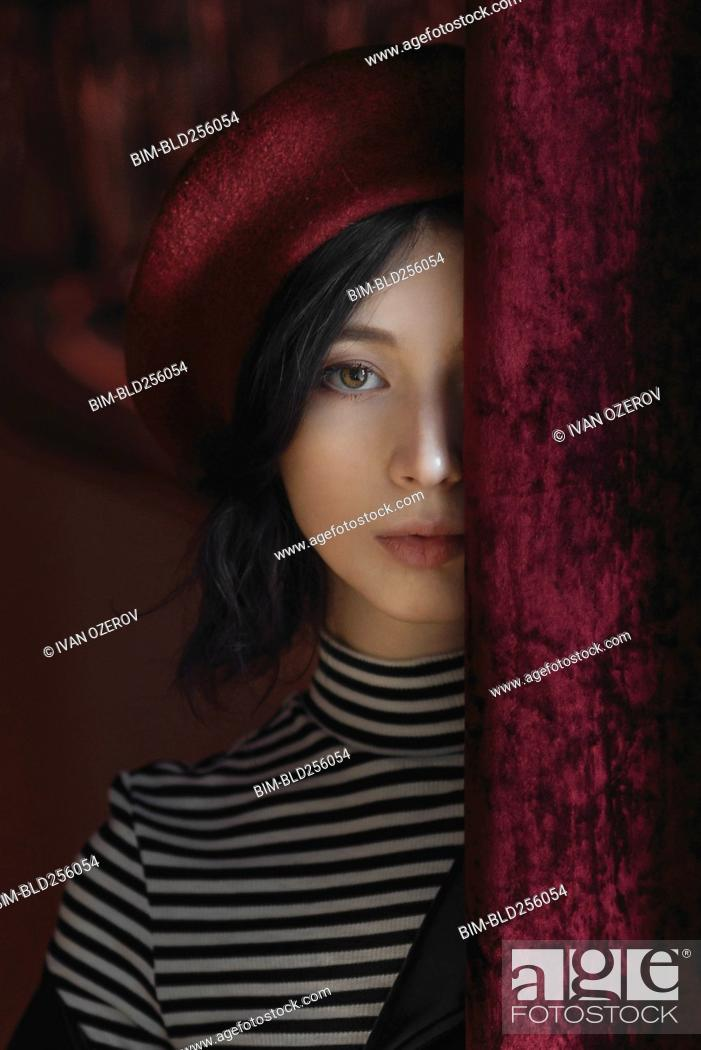 Stock Photo: Caucasian woman peeking from behind curtain.
