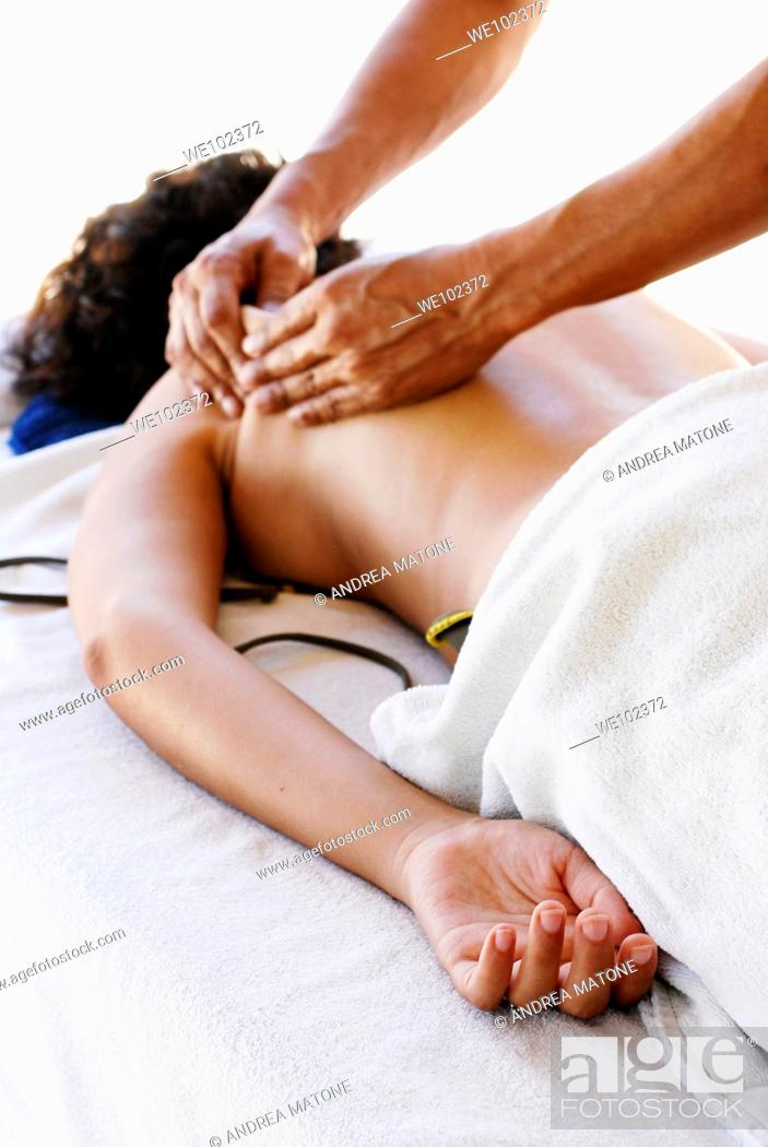 Stock Photo: A man practicing a deep tissue massage on a woman's back.