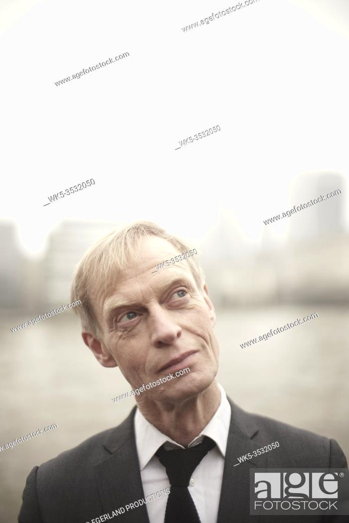 Stock Photo: business man peering aside in London, UK.
