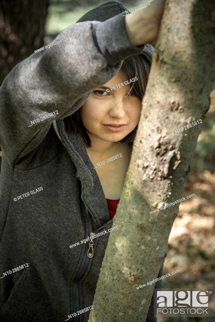 Stock Photo: Young woman, leaning on a tree in a park, wearing a sweatshirt and hoodie.