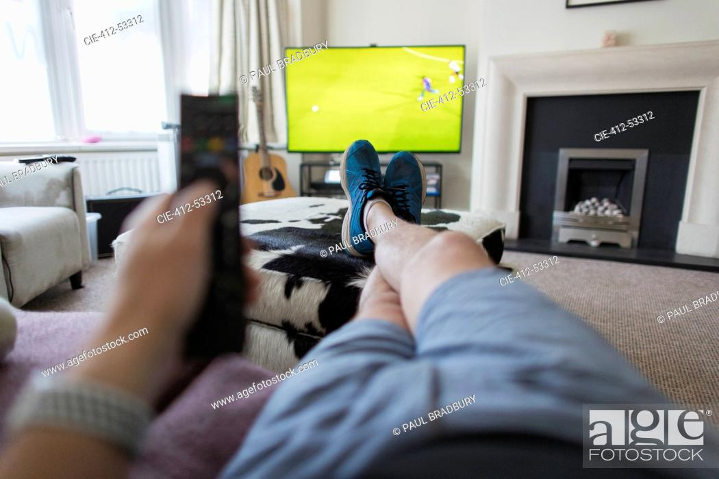 Stock Photo: POV man on sofa with remote control watching soccer match on TV.