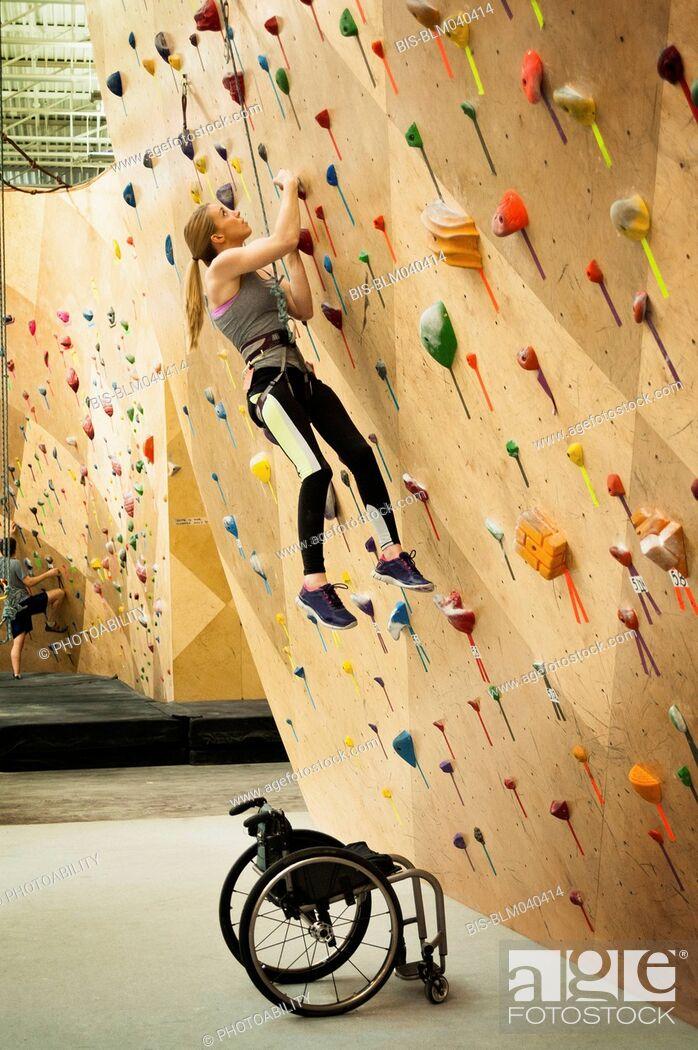Imagen: Paraplegic woman rock climbing in gym.