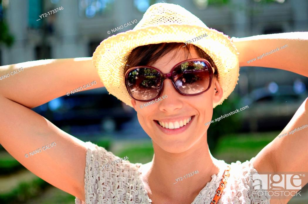 Stock Photo: Attractive young woman with summer style and straw hat in street.