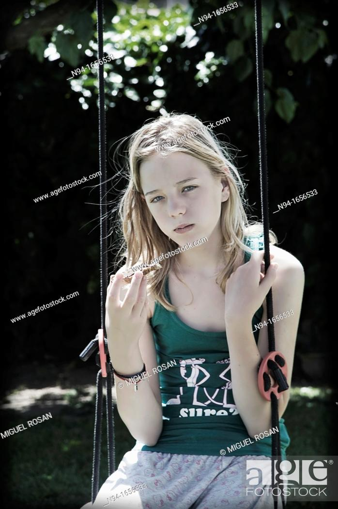 Stock Photo: Blonde teen girl sitting on the swing with a snack.