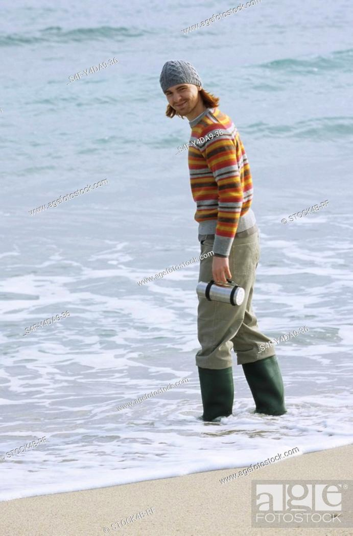 Stock Photo: Young redhaired Man with woolen Hat and Wellies in the Water - Fun - Beach.