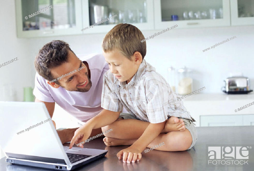 Stock Photo: Father showing son how to use laptop.