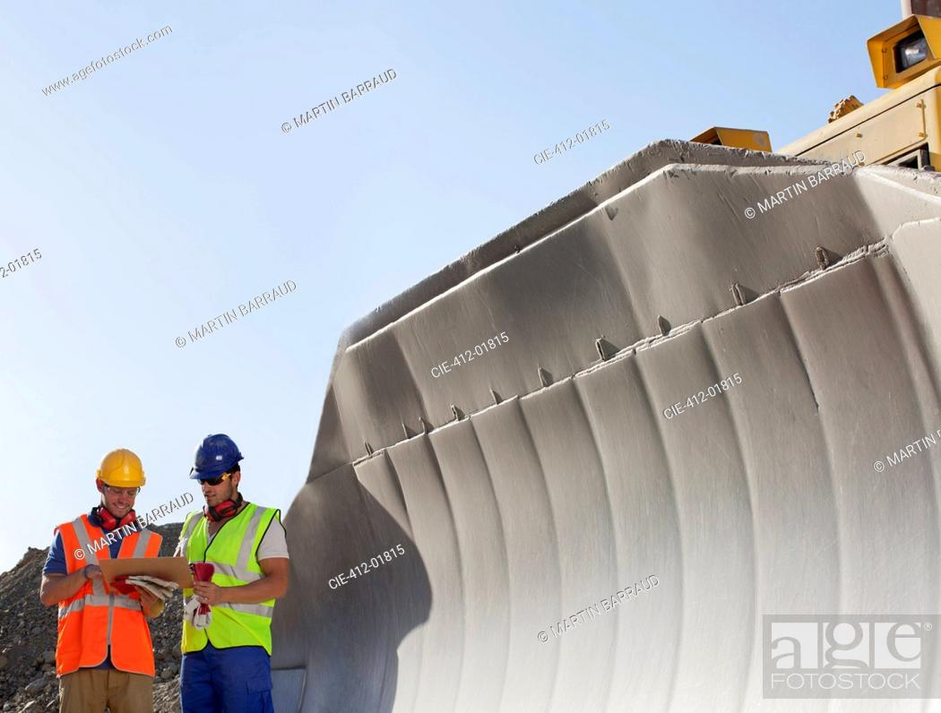 Stock Photo: Workers reading blueprints by digger in quarry.