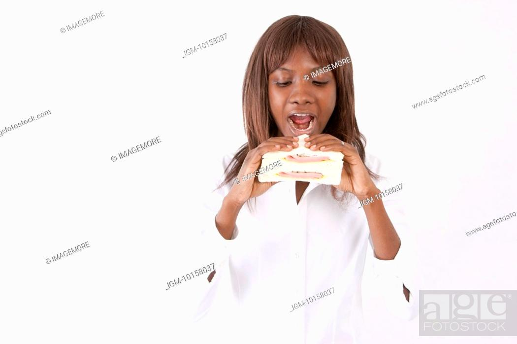 Stock Photo: Young woman holding a sandwich with mouth open.