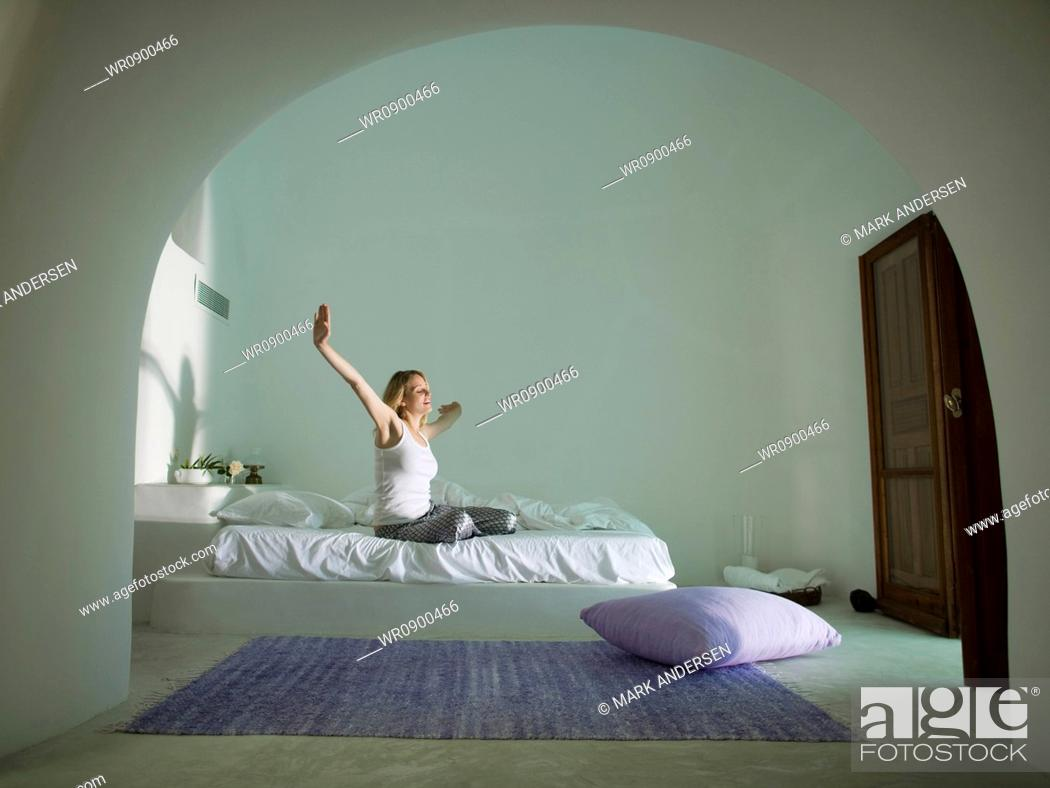 Imagen: Woman sitting on bed stretching.
