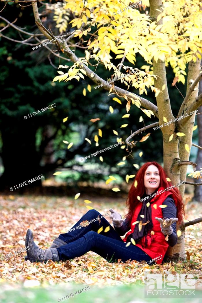 Stock Photo: A young woman sitting beneath a tree in autumn time.