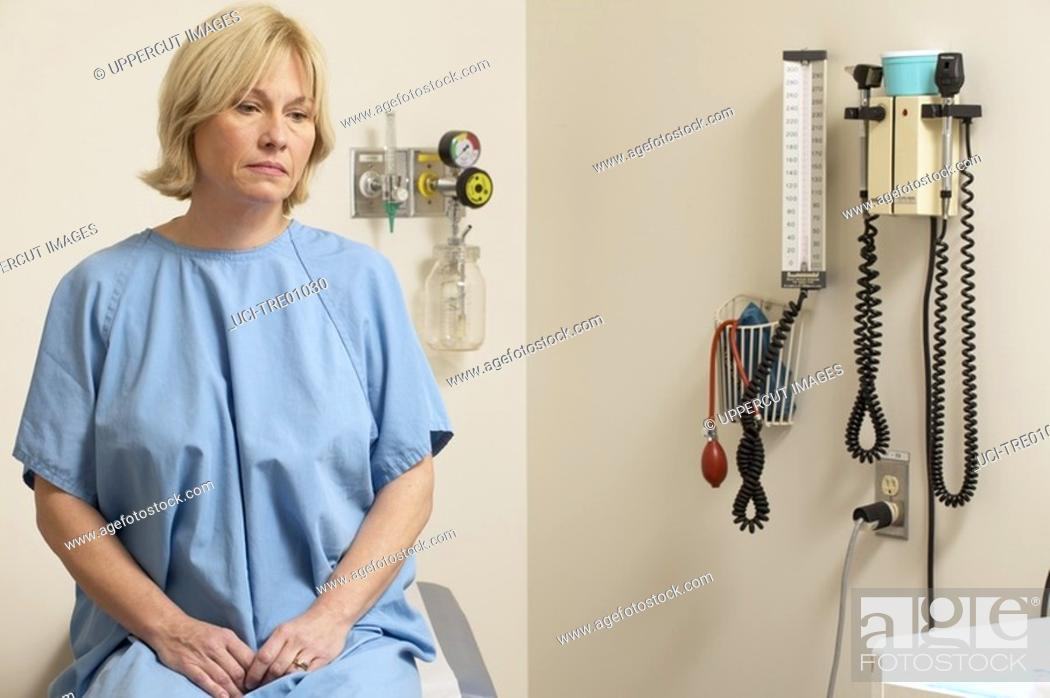 Stock Photo: Forlorn woman sitting on doctor's table.