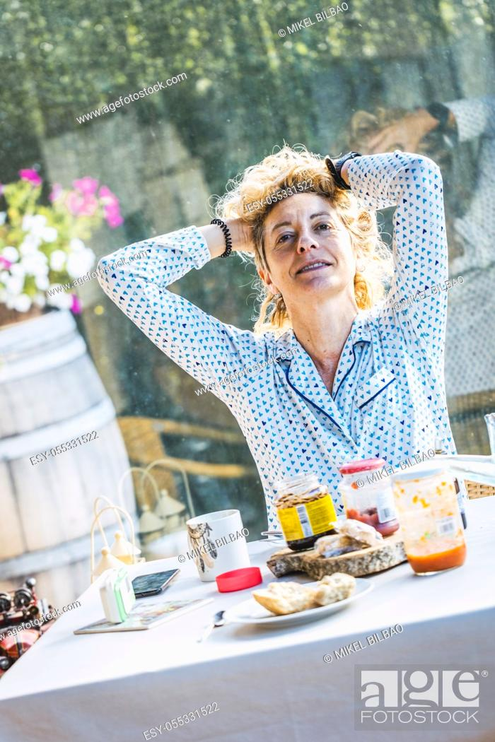 Imagen: Blonde young mature woman in pyjamas at home in breakfast time, self absorbed.
