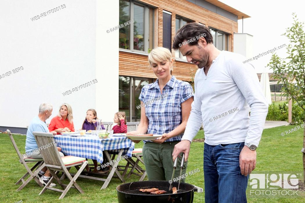 Stock Photo: Germany, Bavaria, Nuremberg, Couple grilling barbecue, family sitting in background.