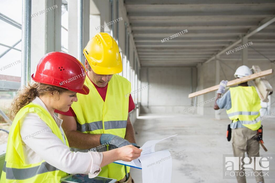Stock Photo: Construction workers with digital tablet and document at building site.