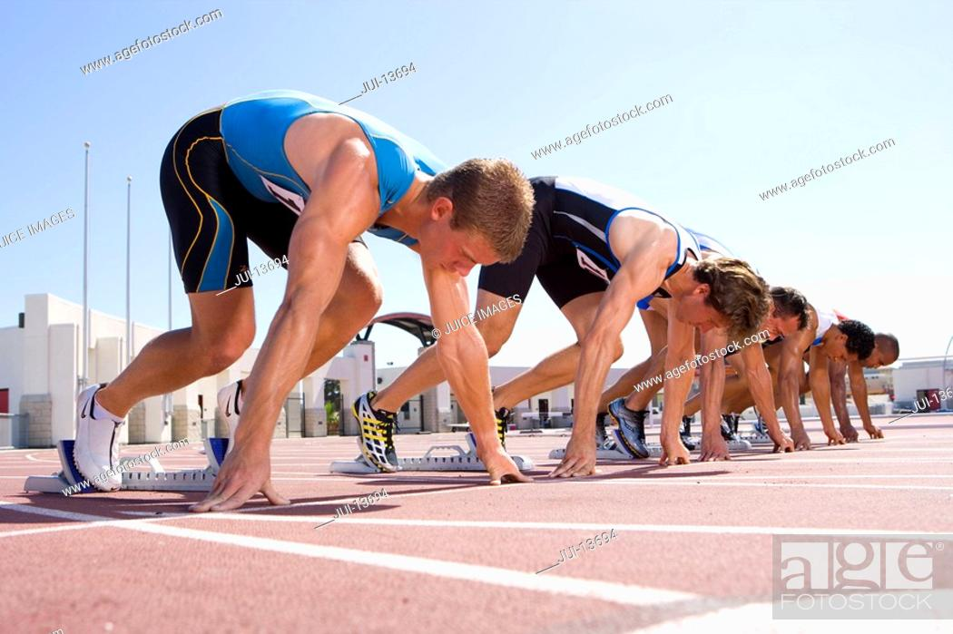 Stock Photo: Male sprinters on starting blocks, low angle view.