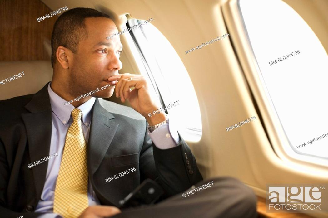 Stock Photo: African American businessman on airplane.