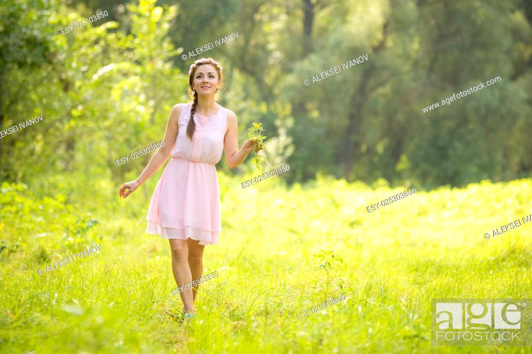 Stock Photo: Young beautiful woman walking on a green meadow with a bouquet of wildflowers in a light summer dress.